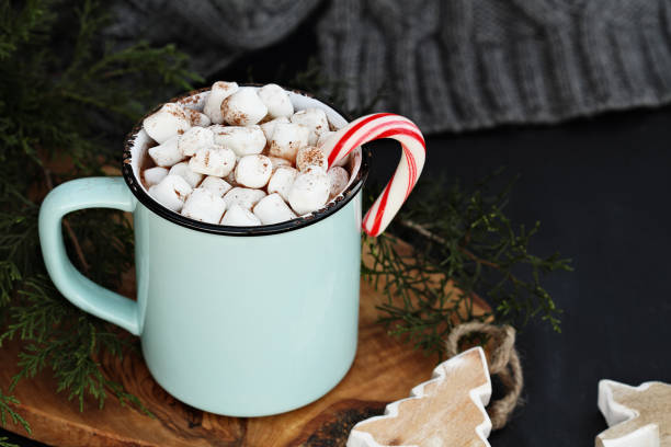 Hot Cocoa and Marshmallows Enamel cup of hot cocoa drink with marshmallows and candy cane against a rustic background with beautiful wood Christmas tree ornaments and a grey scarf. Perfect winter time treat. candy cane stock pictures, royalty-free photos & images