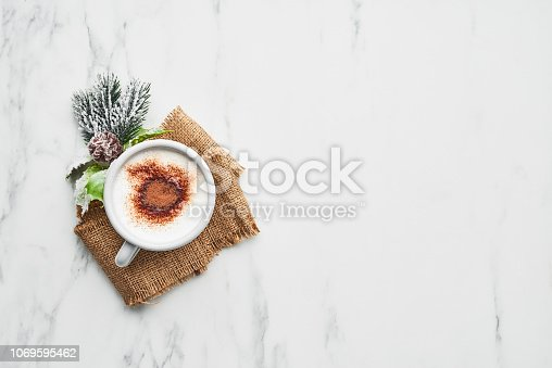 Hot cocoa drink or eggnog. Cup of traditional Christmas drink served on jute over white marble table with copy space.