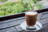 Glass of hot cappuccino chocolate cocoa with teaspoon isolated on wood table background. Summer refreshment drinks concept.