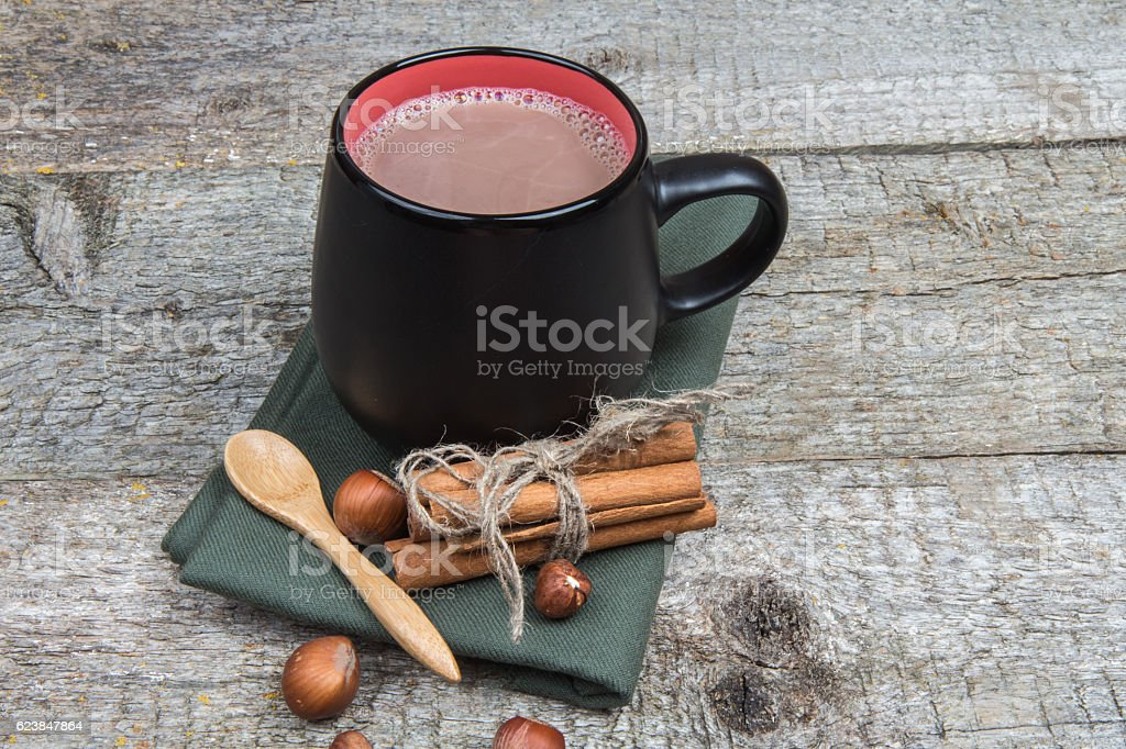 Hot cocoa with cinnamon and hazelnut on rustic wooden background stock photo