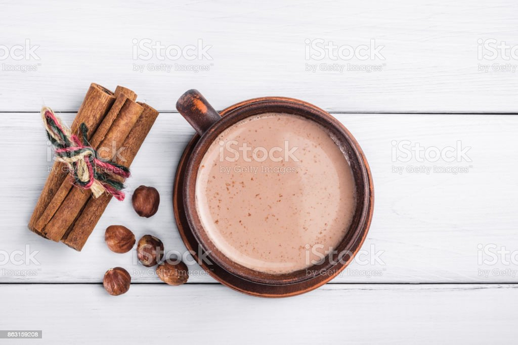 Hot cocoa with milk in brown clay cup, hazelnut and cinnamon sticks on table of white wooden planks, top view stock photo