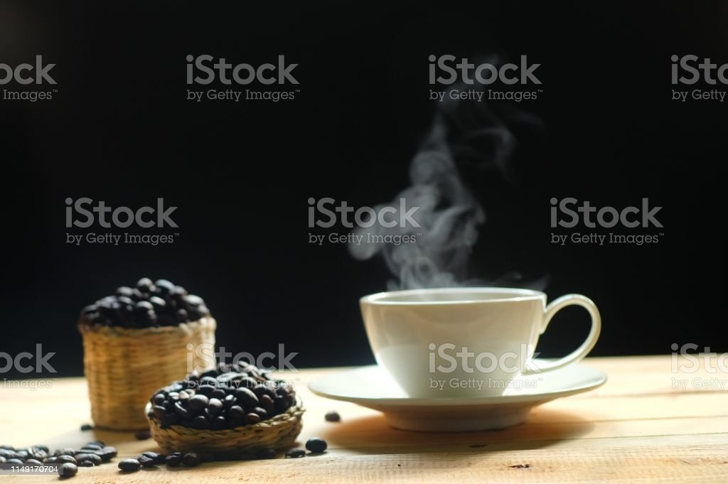 hot coffee and coffee beans with smoke on wooden table dark background