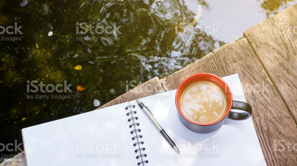 hot coffee, book, and pen place near a pond. stock photo