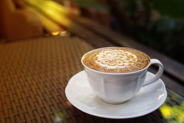 heißen kaffee karamell macchiato cappuccinotasse auf gewebte kaffee gartentisch hintergrund mit warmen morgensonne, geringe schärfentiefe. - www kaffee oder tee stock-fotos und bilder