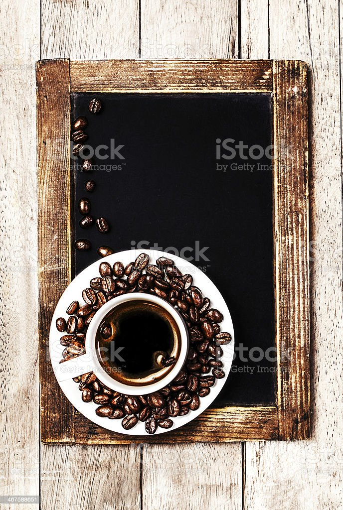 Hot Coffee cup and beans on vintage wooden chalk board. royalty-free stock photo