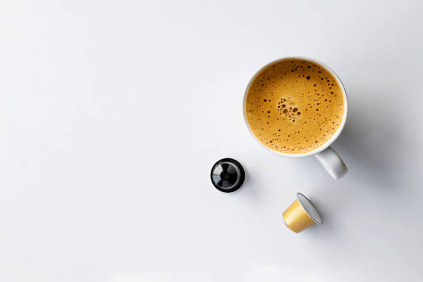 hot coffee cup and capsules on white background – zdjęcie