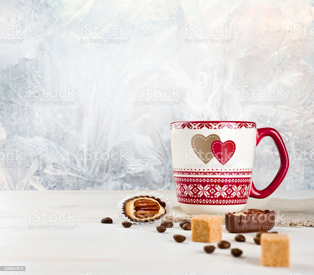 Hot coffee cup and sweets over frosted winter background stock photo