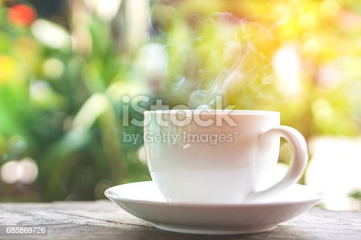 istock hot coffee cup on wooden table over green background 685869726