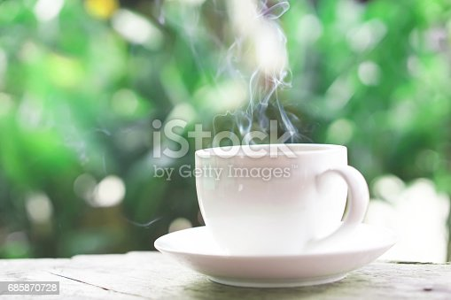 istock hot coffee cup on wooden table over green background 685870728