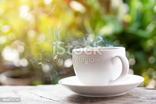 istock hot coffee cup on wooden table over green background 685870742