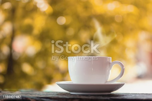 istock hot coffee cup on wooden table over nature autumn background 1154407487