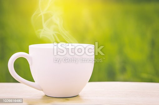 istock hot coffee cup on wooden table over nature green background 1026616480