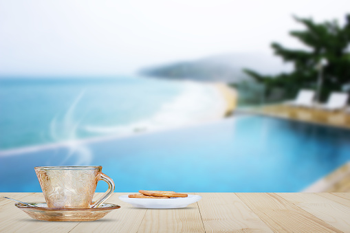 Hot coffee with steam and snack on wooden table top on blurred pool and beach background