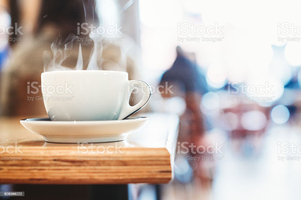 Hot Coffee Cup Steaming on Table stock photo