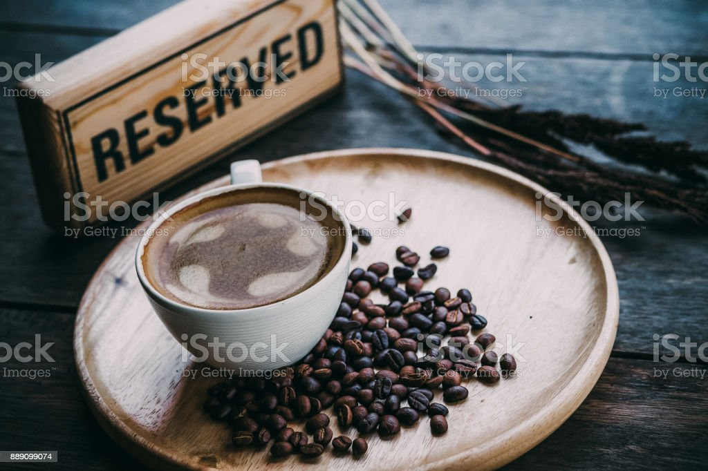 hot coffee cup with coffee bean and reserved sign on wooden theme stock photo