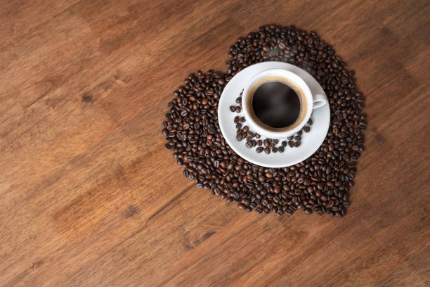 Hot coffee cup with heart pattern of roasted coffee beans stock photo