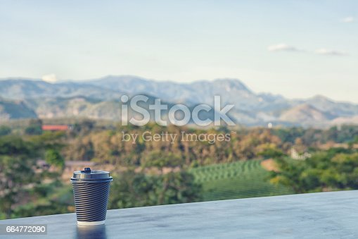 1135319558 istock photo Hot coffee cup with mountrian. 664772090
