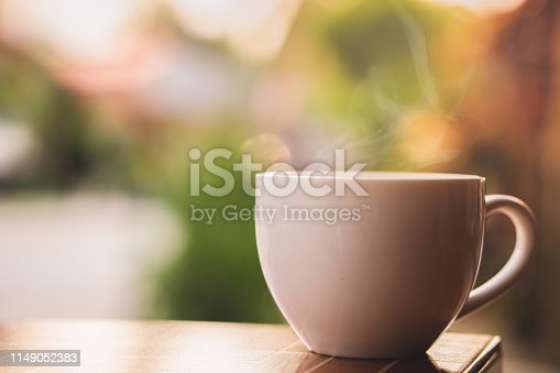 hot coffee cup with smoke in the morning with nature sunlight background