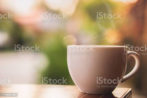 Photo of hot coffee cup with smoke in the morning