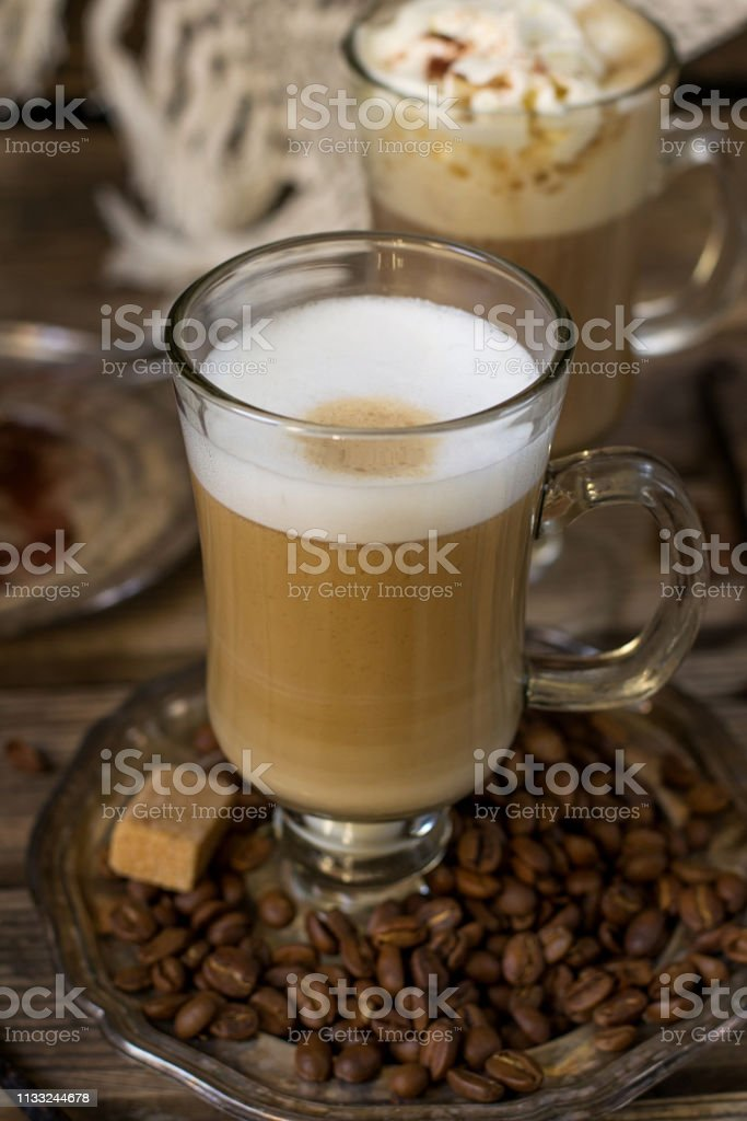 Hot coffee drink cappuccino with milk foam served with coffee beans