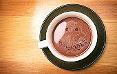 ホットコーヒーを飲みながら、顔に笑顔泡