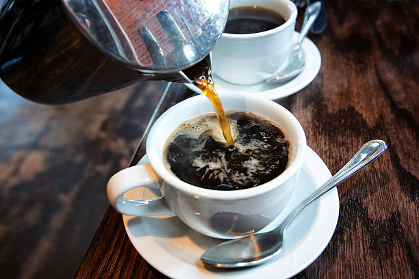 Hot Coffee from a French Press Fresh hot coffee being poured into a cup from a stainless steel french press in a trendy cafe caffeine stock pictures, royalty-free photos & images
