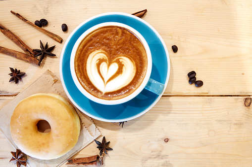 Hot coffee heart in blue cup and donut on wooden