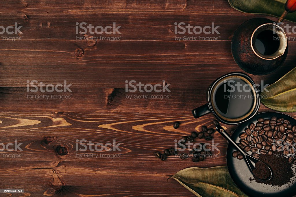 Hot coffee in black cup with beans, dry leaves and turkish pot cezve with copy space on brown old wooden board background, top view. royalty-free stock photo