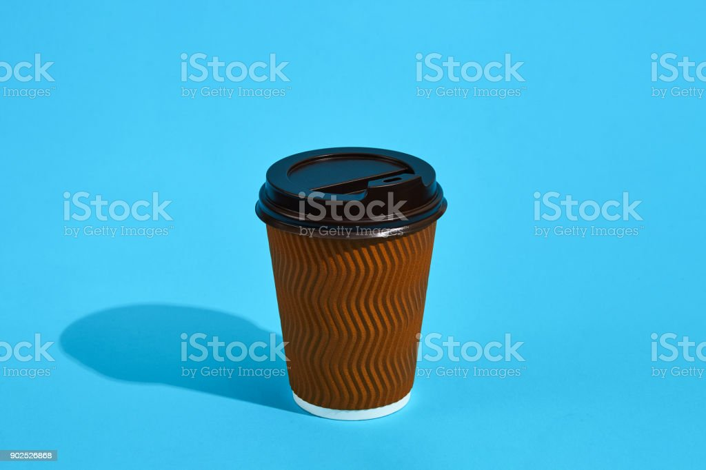 Hot coffee in brown paper cup with black lid on blue background with...