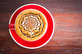 Hot coffee in red cup over wooden table. Latte art in spider shape or like flower. Top view with dark vignette and copy space. Favorite beverage for coffee lover.