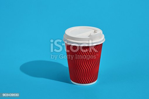 istock Hot coffee in red paper cup with white lid on blue background wi 903409530