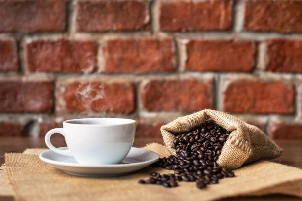 Hot coffee in white cup and roasted coffee beans stock photo