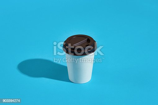 istock Hot coffee in white paper cup with black lid on blue background 903394274