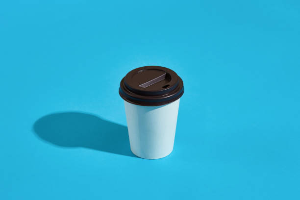 hot coffee in white paper cup with black lid on blue background - paper coffee cup stock photos and pictures