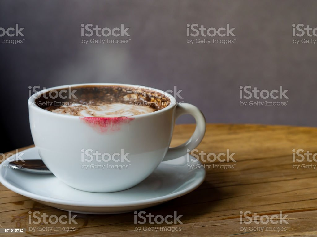 Hot coffee latte with latte art and white smoke in white coffee cup or mug with red lipstick stain on wooden table at coffee shop stock photo