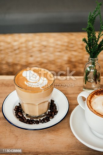 Beautiful hot Coffee Latte with nice milk foam on top and a part of coffee cappuccino cup on wood table, close up shot