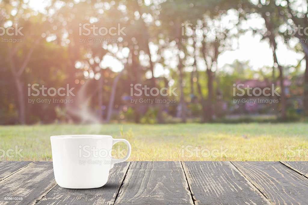 Hot coffee on vintage wooden table top on blurred meadow stock photo