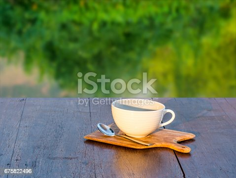 istock Hot coffee on wooden saucer and on wooden table 675822496