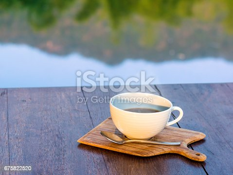 istock Hot coffee on wooden saucer and on wooden table 675822520