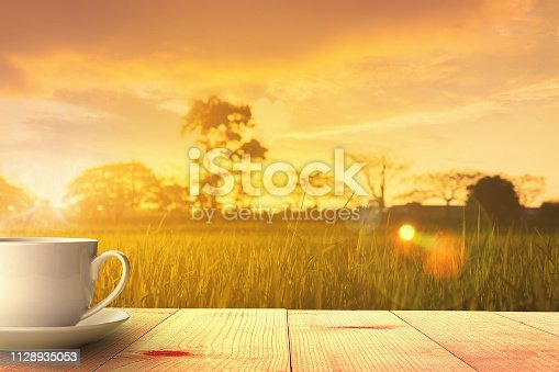hot coffee on wooden table and meadows at sunrise summer nature background