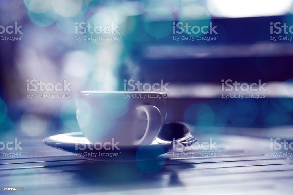 hot coffee on wooden table double exprosure bokeh background .blue tone stock photo