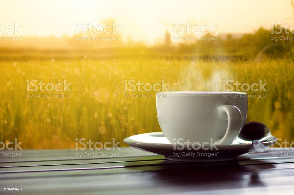 hot coffee on wooden table  meadows background at sunrise stock photo