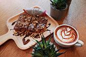 ショコラのパンの上で木製のテーブルでホット コーヒー