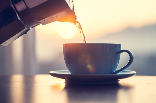 Hot coffee pouring into cup
