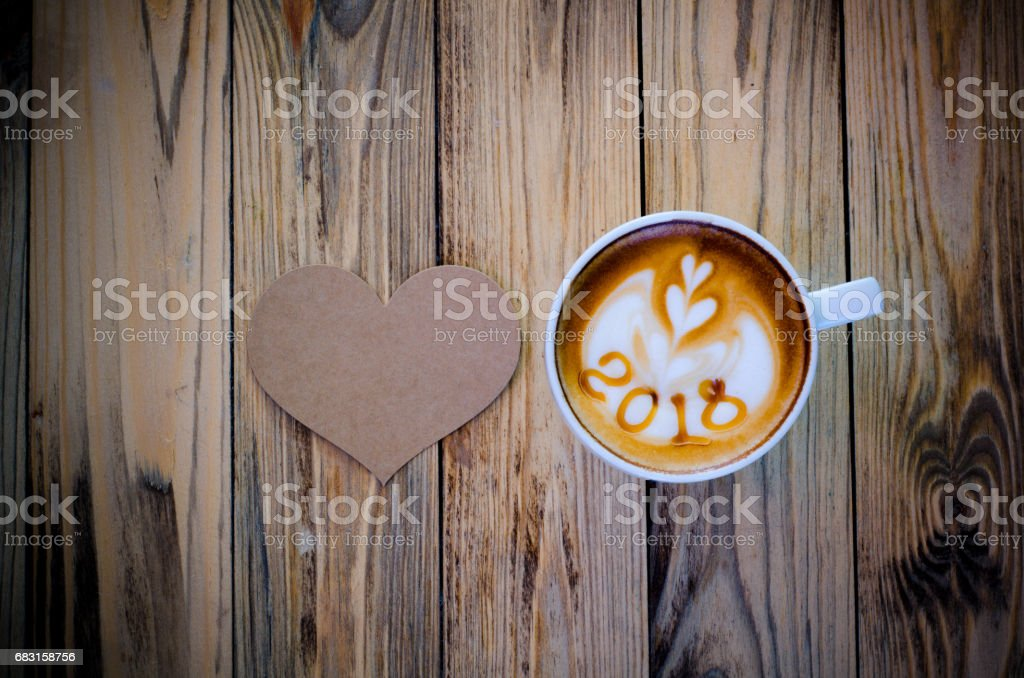 hot coffee with foam milk art 2018 on wooden table royalty-free 스톡 사진