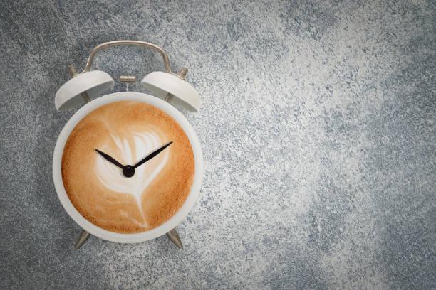 hett kaffe med skummande skum i vit väckarklocka design är kaffe tid koncept - ta en paus bildbanksfoton och bilder
