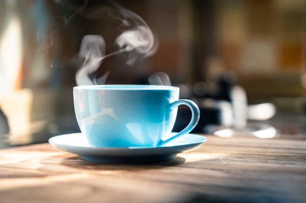 Hot coffee with steam on table stock photo