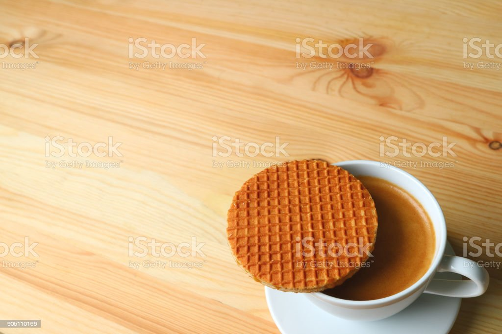 Hot Coffee with Stroopwafel Placed on Top of the Cup Served on Wooden Table, with Free Space for Text or Design stock photo