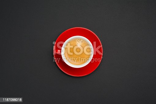 Hot creamy espresso coffee in red cup with saucer isolated on black office desk