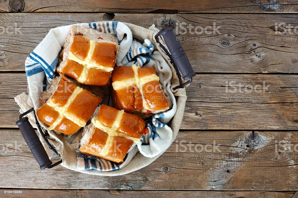 Hot Cross Buns in a basket, over rustic wood stock photo
